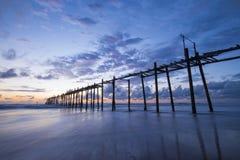 Vieux pont en bois en plage de Natai avec le beau ciel au crépuscule Photographie stock libre de droits