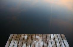 Vieux pont grunge rustique en pilier sur des WI d'un lac de l'eau bleue de noir foncé image libre de droits