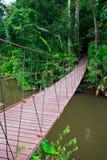 Vieux pont suspendu à travers la rivière Photographie stock libre de droits