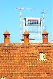 Vieux pot de cheminée trois avec la construction moderne à l'arrière-plan Photographie stock libre de droits