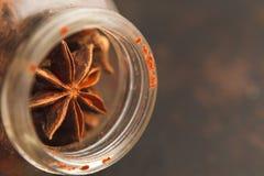 Vieux pot en verre avec des graines d'anis d'étoile sur un fond foncé Images stock
