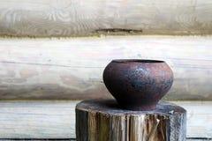 Vieux pot sur le fond d'une cabane en rondins Image libre de droits