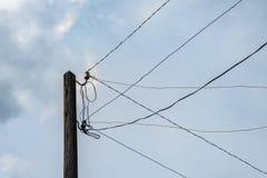 Vieux poteau électrique en bois de rue avec un bon nombre de fils fils électriques contre le ciel bleu image libre de droits