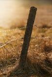 Vieux poteau de barrière avec le fil barbelé et électrique pour le dur de bétail Photos libres de droits