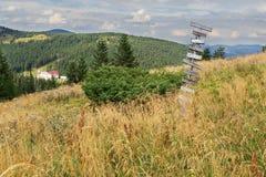 Vieux poteau indicateur en bois dans les montagnes photos stock