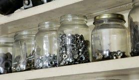 Vieux pots de divers vintage avec des boulons, des écrous et des vis en métal sur le placard en bois dans l'atelier Photo libre de droits