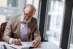 Vieux professeur dans le beau costume prenant des notes dans le carnet Photo stock