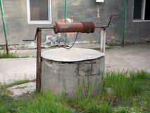 Vieux puits avec la poulie et le seau photos stock