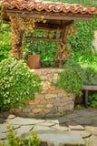 Vieux puits d'eau et un seau en bois parmi des feuilles de lierre Image libre de droits