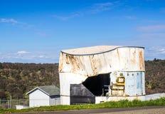 Vieux réservoir d'eau avec le côté ouvert déchiré Photos libres de droits