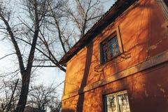 Vieux rétro mur de maison avec des fenêtres à la lumière du soleil de coucher du soleil Jour chaud d'automne Images stock