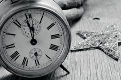 Vieux réveil et étoile sur une surface en bois rustique, dans le noir Images stock