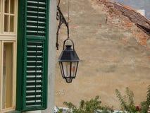 Vieux réverbère et un volet vert Photos libres de droits