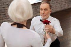 Vieux retraité sûr exprimant l'amour à la femme en salle de bal Images stock