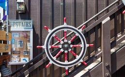 Vieux rouge et le blanc embarque la roue sur le mur Photo stock