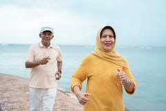 Vieux séance d'entraînement et fonctionnement musulmans de couples à la plage images stock