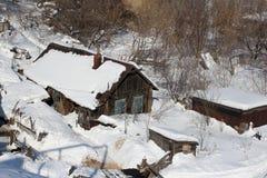Vieux s'est dégradée la neige en bois de maisons couverte en hiver photographie stock libre de droits