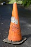 Vieux sale porté trafiquent le cône sur la route goudronnée Photographie stock