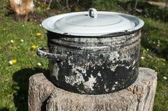 Vieux sauserpot en métal sur le rondin en bois Photographie stock libre de droits