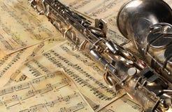 Vieux saxophone et notes Photos stock