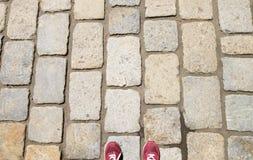 Vieux sentier piéton en pierre et un homme dans des chaussures rouges Photographie stock libre de droits