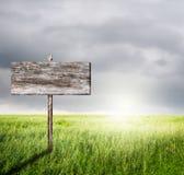 Vieux signe en bois avec l'herbe et les rainclouds de pente Photos stock