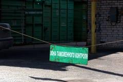 Vieux signe rouillé vert de secteur de douane à l'entrée au dédouanement avec l'inscription dans le Russe avec l'autorail de fret photo stock