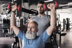 Vieux sportif sérieux faisant des exercices dans le gymnase moderne avec l'entraîneur Images stock