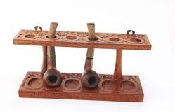 Vieux stand en bois découpé de pipe avec des pipes photographie stock libre de droits