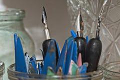 Vieux stylos en métal et spatules en plastique pour la poterie en plan rapproché en verre de pot Image stock