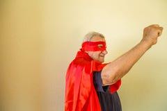 Vieux superhéros soulevant le poing Images stock