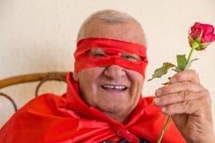 Vieux superhéros tenant la rose de rouge Images libres de droits
