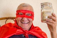 Vieux superhéros tenant le pot d'argent Photographie stock