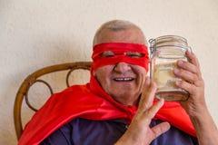 Vieux superhéros tenant le pot d'argent Photographie stock libre de droits