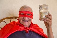 Vieux superhéros tenant le pot d'argent Images stock
