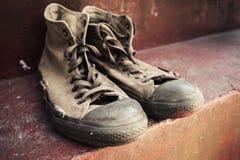 Vieux support d'espadrilles sur les escaliers concrets Photographie stock libre de droits