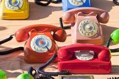 Vieux téléphone analogue en plastique coloré sur un marché aux puces Photographie stock libre de droits