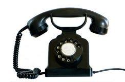 Vieux téléphone noir sur le blanc. Images stock