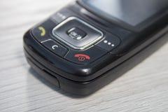 Vieux téléphone portable Une clé avec un combiné rouge dans le premier plan photos stock