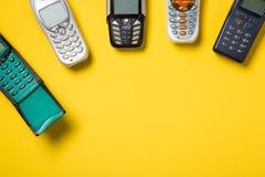 Vieux téléphones portables sur le fond jaune avec l'espace libre pour votre texte photo stock