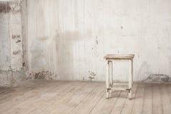 Vieux tabouret minable dans un intérieur abandonné Photo stock