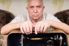 Vieux tailleur sérieux Guy Leaning sur la machine à coudre Images libres de droits