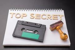 Vieux tampon en caoutchouc en bois et cassette sonore sur un morceau blanc de carnet Enregistrements secrets des entretiens polit image stock