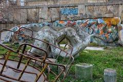 Vieux terrain de jeu abandonné avec le graffiti et le rond point rouillé Images stock
