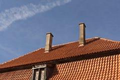 Vieux toit carrelé avec les cheminées et la fenêtre contre le ciel bleu photo libre de droits