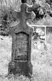 Vieux tombestone tordu superficiel par les agents de Christian Catholic au cimetière en noir et blanc photo stock