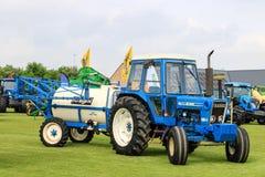 Vieux tracteur bleu du gué 7600 tirant des pulvérisateurs d'une culture de chevalier à l'exposition image libre de droits