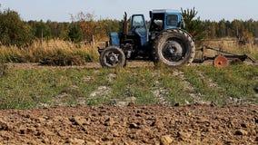 Vieux tracteur de vintage labourant la terre banque de vidéos