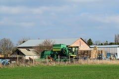 Vieux tracteur et moissonneuse dans un hangar de brique Stockez le vieil équipement Photographie stock
