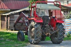 Vieux tracteur rouge avec le chargeur Image libre de droits